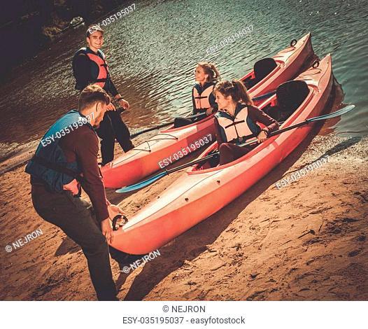 Cheerful friends having fun in kayaks on a beach
