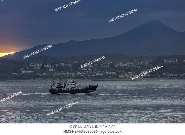 France, Pyrenees Atlantiques, Euskadi, Pays Basque, Hendaye, return to port for a fishing boat under a cloudy sky