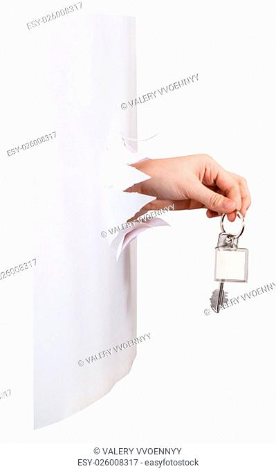 side view of hand holds the keychain through a hole in a sheet of paper isolated on white background