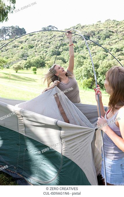 Two young females friends constructing tent