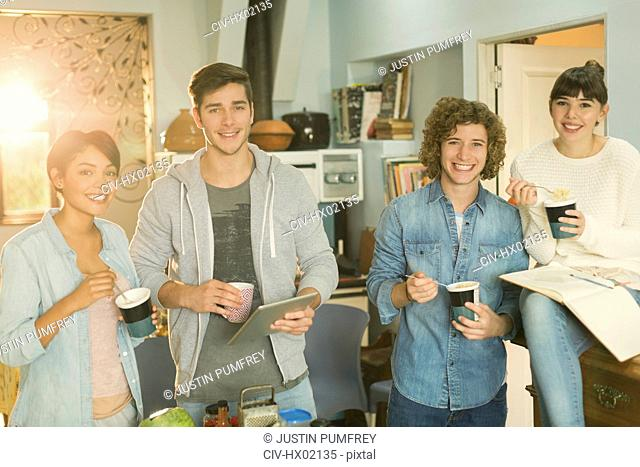 Portrait smiling young college student roommates studying eating instant noodles in apartment