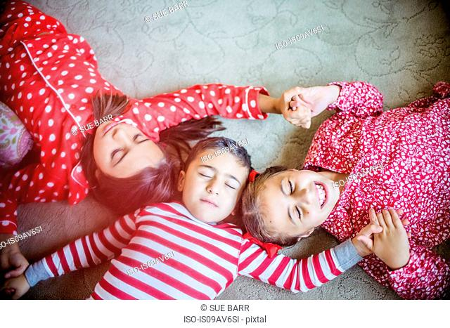 Overhead view of children wearing pyjamas lying on carpet holding hands eyes closed