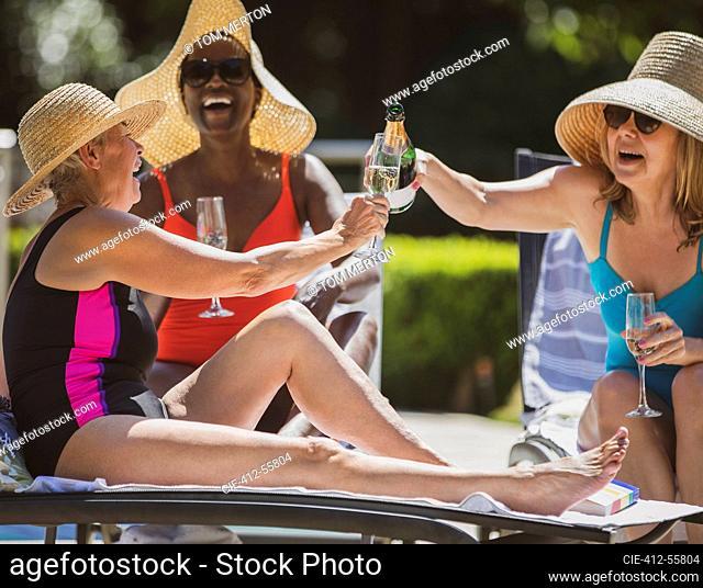 Happy senior women friends drinking champagne on sunny summer patio