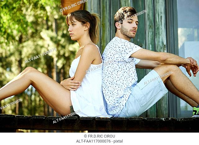 Angry young couple sitting in park