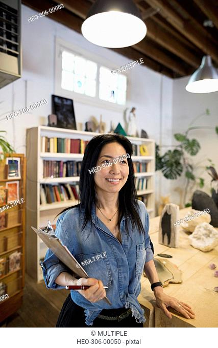 Smiling female shop owner with clipboard