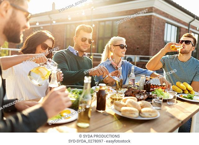 friends having dinner or bbq party on rooftop
