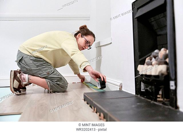 Woman measuring space fit new floor boards