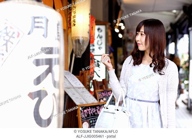Fashionable Japanese woman at a traditional shopping street, Tokyo, Japan