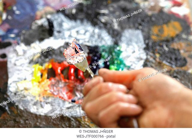 Hand holding used spatula in front of artist's palette