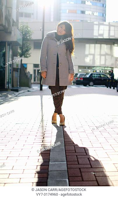 Japanese Girl poses on the street in Ginza, Japan. Ginza is a shopping city located in Tokyo