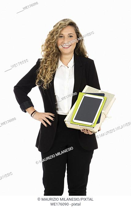 Businesswoman standing in the studio with tablet and documents in her arms, she is wearing a black suit and a white shirt