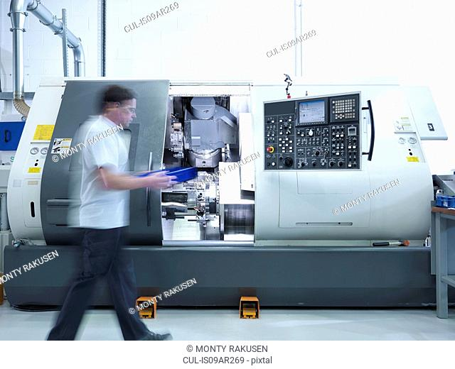 Engineer working with CNC lathe in factory