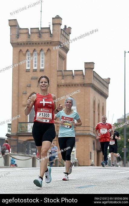 12 September 2021, Hamburg: Athletics: Marathon: Marathon runners in front of the Speicherstadt. Photo: Michael Schwartz/dpa