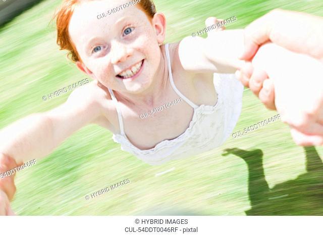 Parent swinging daughter in grass