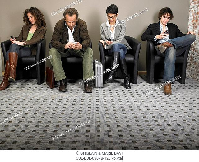 Two businesswomen and two businessmen sitting in waiting room