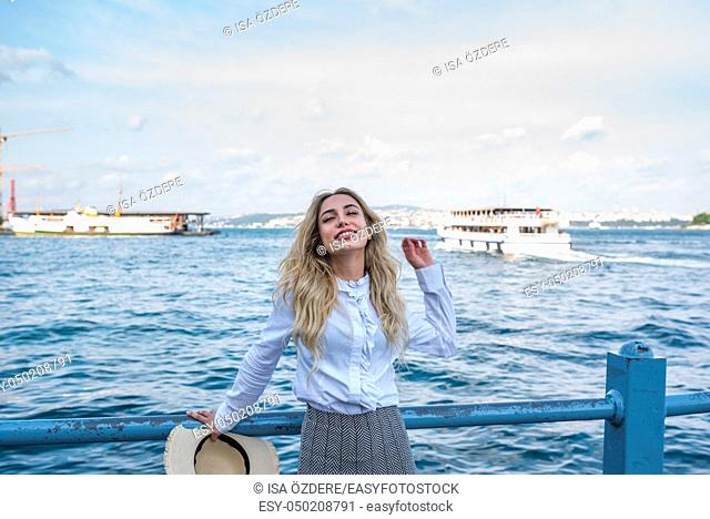 Attractive young beautiful girl poses near bosphorus with view of Istanbul, Turkey. Traveler concept
