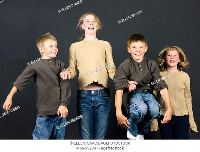 Four Caucasian brothers and sisters jumping up in the air for joy