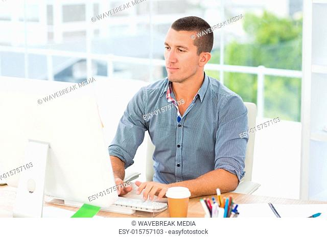 Handsome businessman typing on a computer