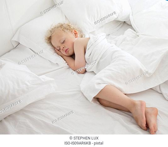 Young boy asleep on bed, under cover