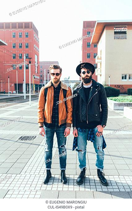 Portrait of two young male hipster friends standing in city housing estate, full length