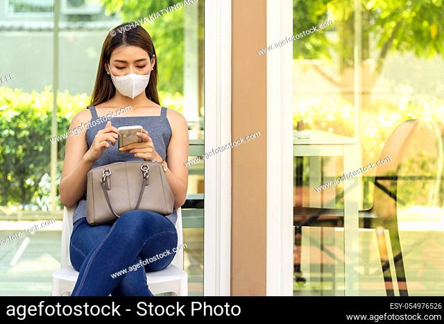 Asian woman customer wear face mask using her mobile phone while sit in waitting social distance queue in front of restaurant with free copyspace for editing