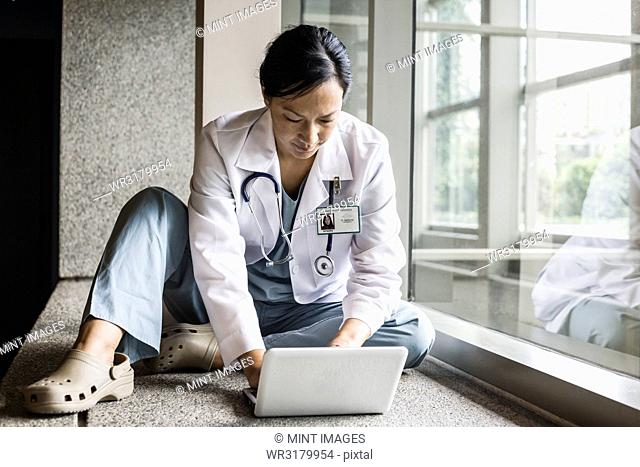 Asian woman doctor working on a lap top in a hospital hallway
