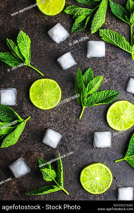 Green mint leaves, ice cubes and sliced lime on black table. Top view