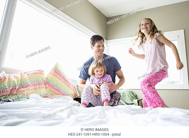 Father and daughters playing on bed