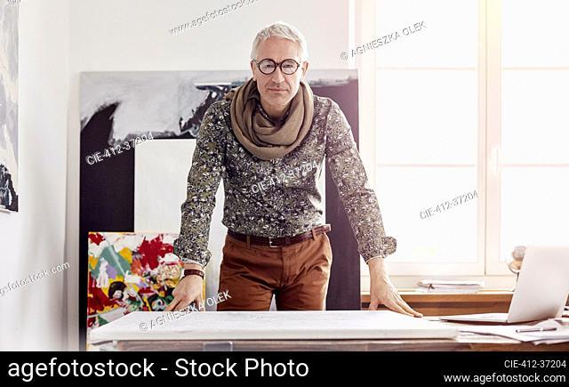 Portrait confident male photographer standing over canvas in art studio