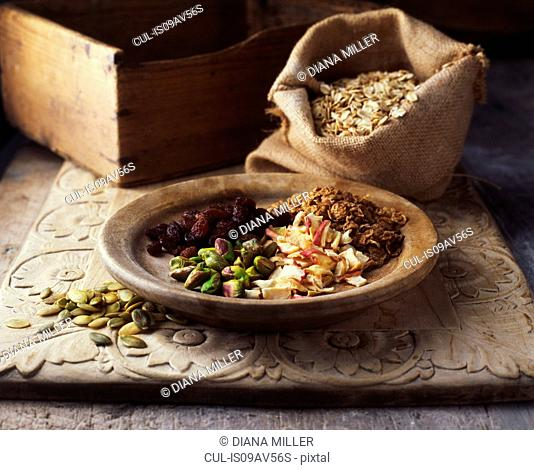 Dried fruits and nuts on wooden plate with burlap sack of oats