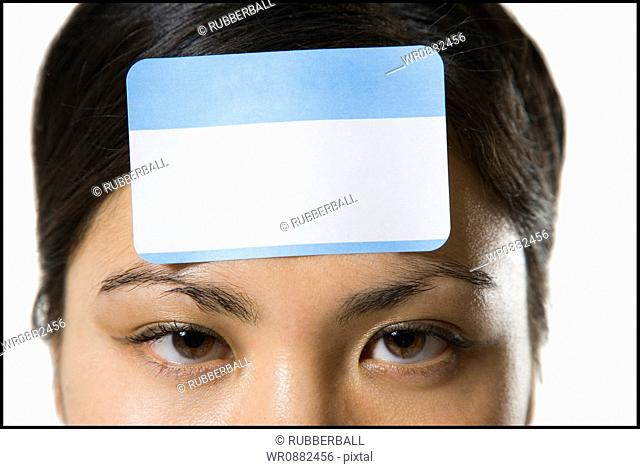 Portrait of a young woman with a blank name tag on her forehead