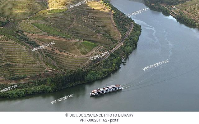 Aerial footage of a boat on the Douro river, with vineyards on the riverbank. Filmed in Portugal