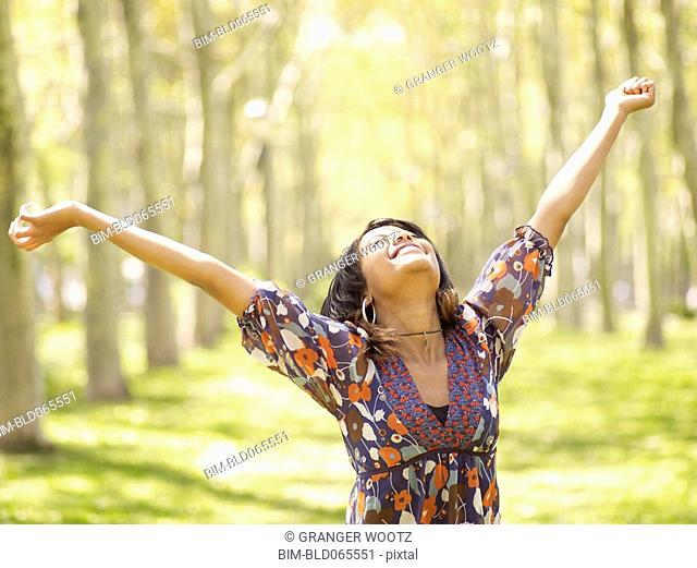 Hispanic woman with arms outstretched in park