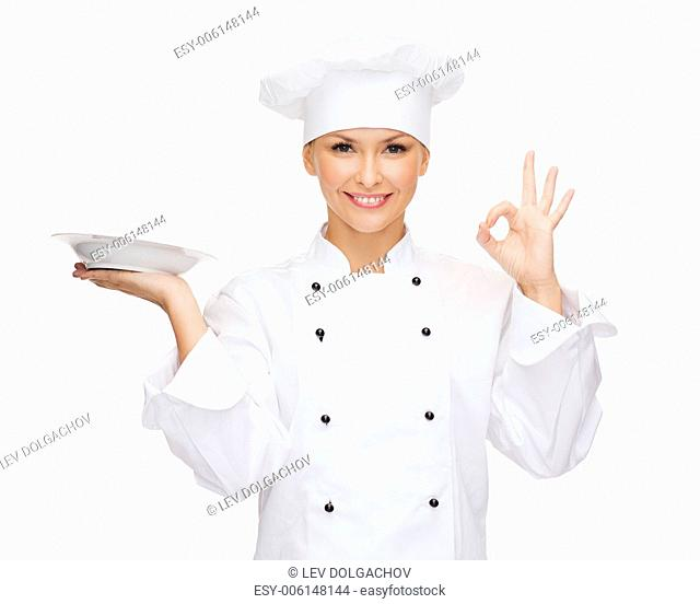 cooking and food concept - smiling female chef, cook or baker with empty plate showing ok sign