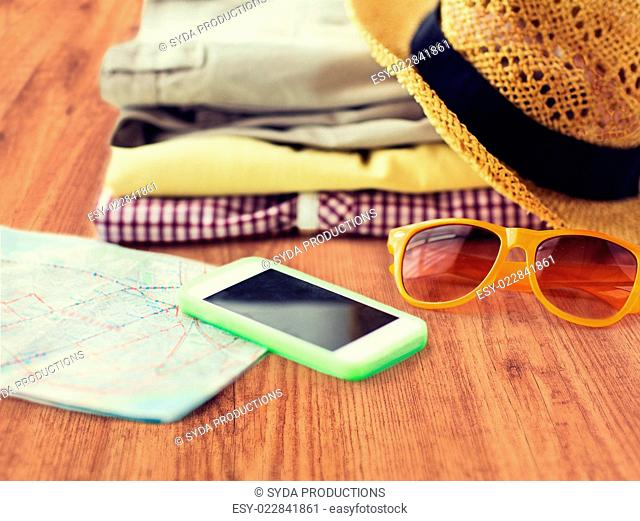 travel, summer vacation, tourism and objects concept - close up of folded clothes, smartphone and touristic map on wooden floor