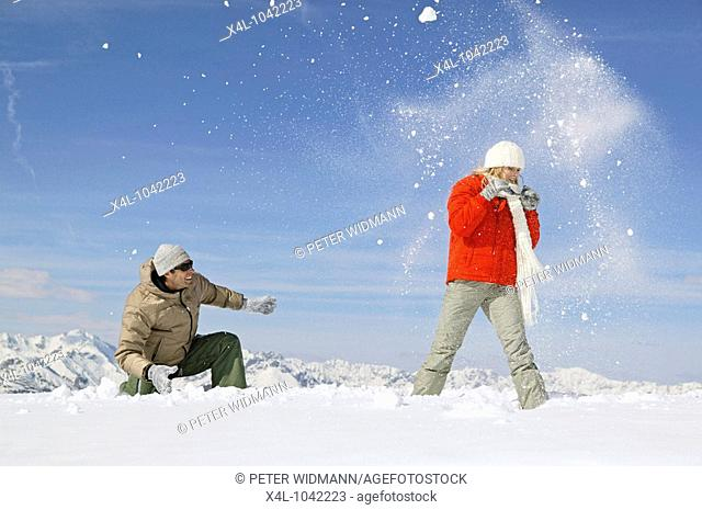 Young couple has fun with a snowball fight