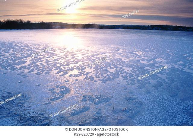 Rising sun glinting off fresh ice patterns in bay of Vermillion river. Naughton. Ontario. Canada