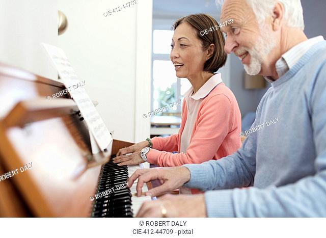 Active senior couple playing piano