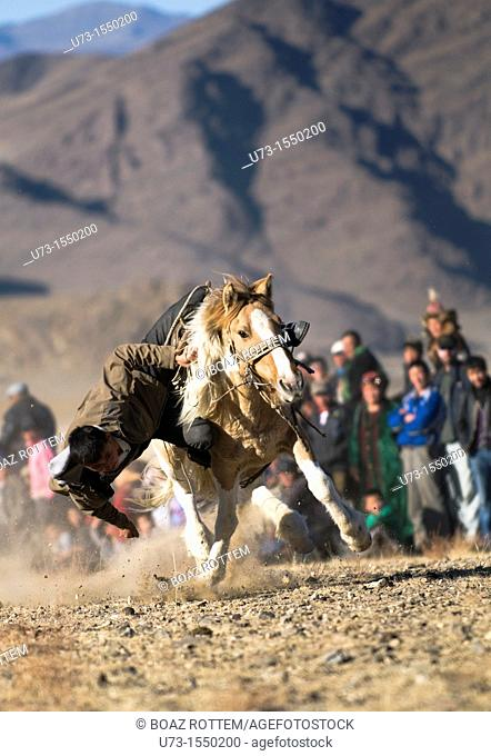 tenge alu, a traditional Kazakh sport where the rider tries to pick up tokens without falling off his horse competition at the Kazakh Eagle Hunters' Festival in...