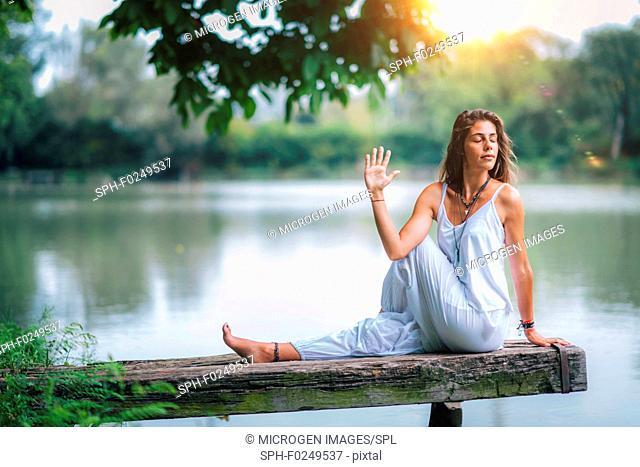 Woman doing yoga by a lake