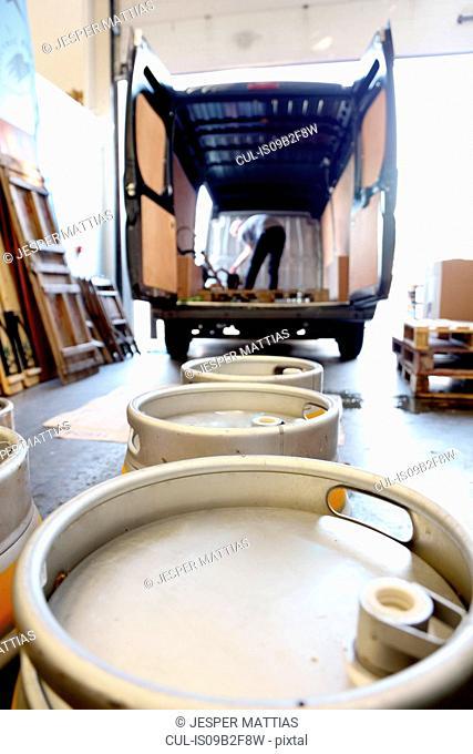 Worker in brewery, preparing to distribute barrels of beer