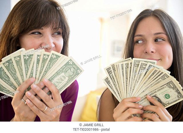 Teenage girl (14-15) and her mom holding dollar bills