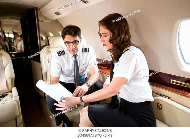 Male and female pilots checking flight plan in cabin of private jet