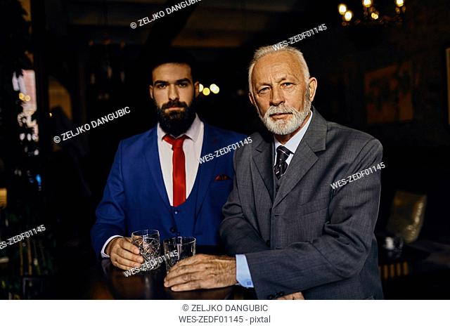 Portrait of two elegant men in a bar with tumblers