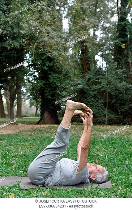 an older woman doing yoga outdoors