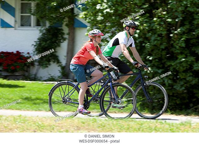 Man and teenage girl on a bicycle tour with trekking bikes