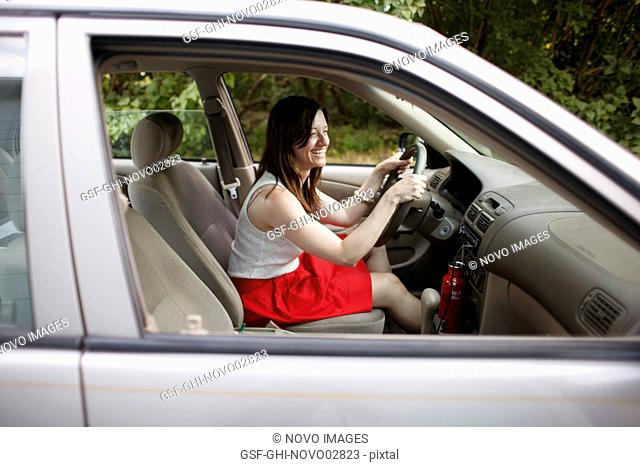Smiling Woman Sitting Behind Steering Wheel in Car