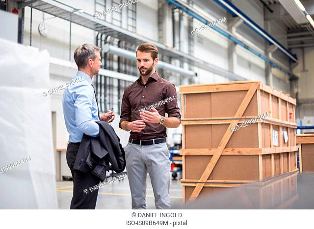 Manager and supervisor having meeting in distribution warehouse