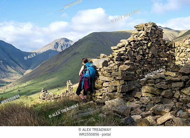 Crumbling stone houses in the English Lake District in Wast Water with views of Kirk Fell and Great Gable in the distance, Lake District National Park, Cumbria