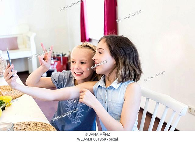 Two girls taking a selfie at table